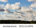 the plane is in the clouds over ... | Shutterstock . vector #1011111094