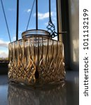 Small photo of A vintage amber glass candle holder, in window ledge.