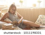 young woman reading book at home | Shutterstock . vector #1011198331