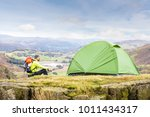 man explorer with a tent at top ... | Shutterstock . vector #1011434317