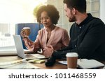 two smiling colleagues sitting... | Shutterstock . vector #1011468559