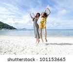 woman jumping together on sand beach with blue sky background - stock photo
