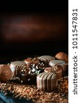Small photo of Handmade dark milk chocolates set against a dark rustic background with differential focus and generous accommodation for copy space.