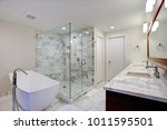 Small photo of Sleek bathroom features freestanding bathtub paired with floor-mounted faucet atop marble floor placed in front of glass shower accented with gray marble surround.