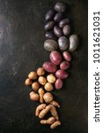 Small photo of Variety of raw uncooked organic potatoes different kind and colors red, yellow, purple over dark texture background. Top view, space