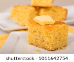 Stock photo piece of freshly baked cornbread with creamy butter on top 1011642754