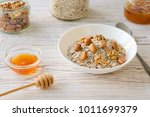 bowl of muesli and nuts with... | Shutterstock . vector #1011699379