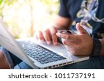 man shopping online with laptop ... | Shutterstock . vector #1011737191