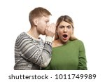 Small photo of Portrait of mysterious young fair-haired male with stubble covering ear of his shocked girlfriend who is listening to gossips, rumours, confidential information and secrets with eyes full of disbelief