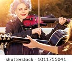 Small photo of Music on violin by woman perform in park outdoor. Girl performing jazz on city street. Color tone on shiny sunlight background. Spring outside with blue hairstyle background. Toning of spring photo.