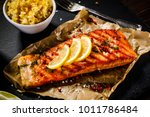 Stock photo grilled salmon with vegetables served on black stone plate on wooden table 1011786484