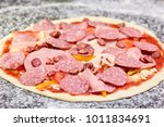 Unbaked Pizza With Many Sliced...