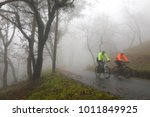 two cyclists riding up wet and... | Shutterstock . vector #1011849925