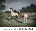 free horse runs around a women. ...