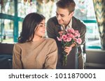 the happy man giving flowers to ... | Shutterstock . vector #1011870001