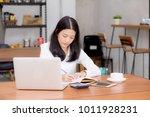 business asian woman writing on ... | Shutterstock . vector #1011928231