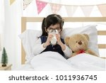 little asian girl drinking some ... | Shutterstock . vector #1011936745