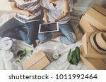 young happy couple moving in... | Shutterstock . vector #1011992464