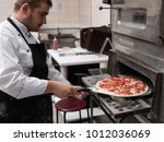 cheff cooking pizza and putting ... | Shutterstock . vector #1012036069