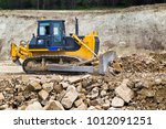 Small photo of The bulldozer moves and spreads the soil and rubble on the embankment of the road. Work bulldozer on the construction of a highway.. Road under construction.