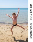 Small photo of Six-year-old boy in black speedo jumping into the sea and laughs.