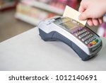 hand swiping credit card on... | Shutterstock . vector #1012140691