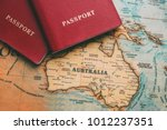 Small photo of Two passports on map. Travel to Australia
