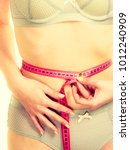 Small photo of Woman slim girl in lingerie measuring her waist with measure tape closeup