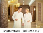 a couple in the bathrobes at... | Shutterstock . vector #1012256419