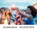 Small photo of Happy friends taking selfie with smartphone at beach party outdoor - Young people having fun at kiosk bar drinking champagne - Soft focus on mobile cell phone - Youth lifestyle and vacation concept