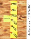 """Small photo of Stickers with abbreviation expansion for word """"Autism"""" on wooden background"""