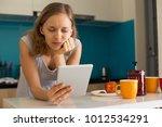 sad pretty woman using tablet... | Shutterstock . vector #1012534291