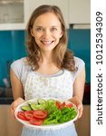 smiling woman holding plate...   Shutterstock . vector #1012534309