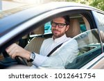 Stock photo smiling young man wearing glasses sitting behind the wheel of his car driving through the city 1012641754
