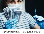 money and syringe in the hands... | Shutterstock . vector #1012654471