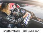 young woman sits behind wheel... | Shutterstock . vector #1012681564