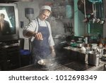 male chef roasting and... | Shutterstock . vector #1012698349