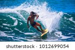 riding the waves. costa rica ... | Shutterstock . vector #1012699054