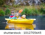 child with paddle on kayak.... | Shutterstock . vector #1012705645