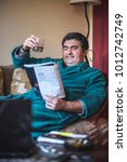 Small photo of Mature man enjoying some light read, entertained by an article in a magazine, drinking alcohol and relaxing