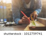Small photo of Carpenter working on woodworking machines in carpentry shop. A man works in a carpentry shop.