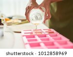 close up image of woman pouring ... | Shutterstock . vector #1012858969