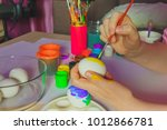 woman painting on easter egg.... | Shutterstock . vector #1012866781