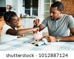 dad and daughter saving money... | Shutterstock . vector #1012887124
