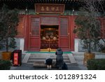 """Small photo of Editorial Beijing, China - January 24, 2018: Guangji temple is the key cultural relics protection units Chinese. Pious man kowtow in front of a temple to pray for blessing, chinese is a """"virtue box"""""""