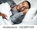 a man sleeping on a bed   Shutterstock . vector #1012897159