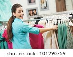 Young woman choosing shirt and blouse during clothing shopping at store - stock photo