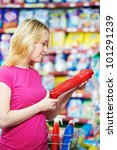 Happy smiling woman choosing personal care items and goods in front of household chemistry produces in shopping supermarket - stock photo
