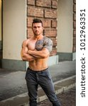 Small photo of Handsome muscular shirtless man with tattoo posing in European city center, Turin, Italy. Tattoo reads: We are free to start again, in Italian