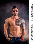 Small photo of Handsome shirtless muscular man with jeans, standing and wearing sunglasses, on dark smoky background in studio shot. Tattoo reads: We are free to start again, in Italian